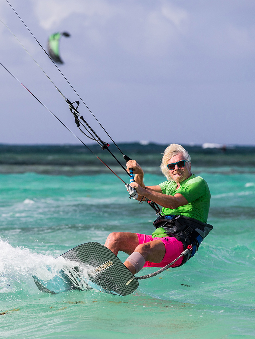 An action shot of Richard Branson hand-gliding on the ocean.
