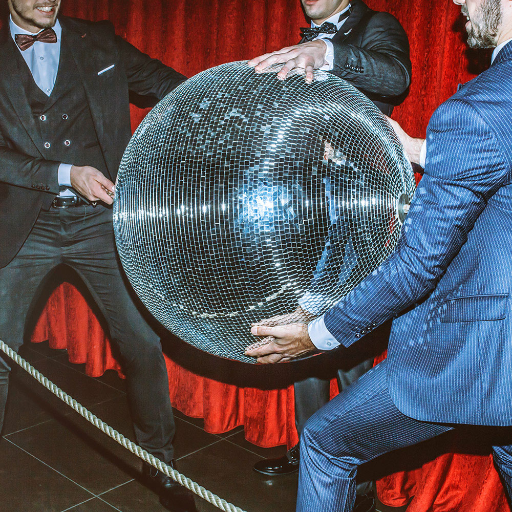 Three men in dapper suites holding an oversized disco ball.