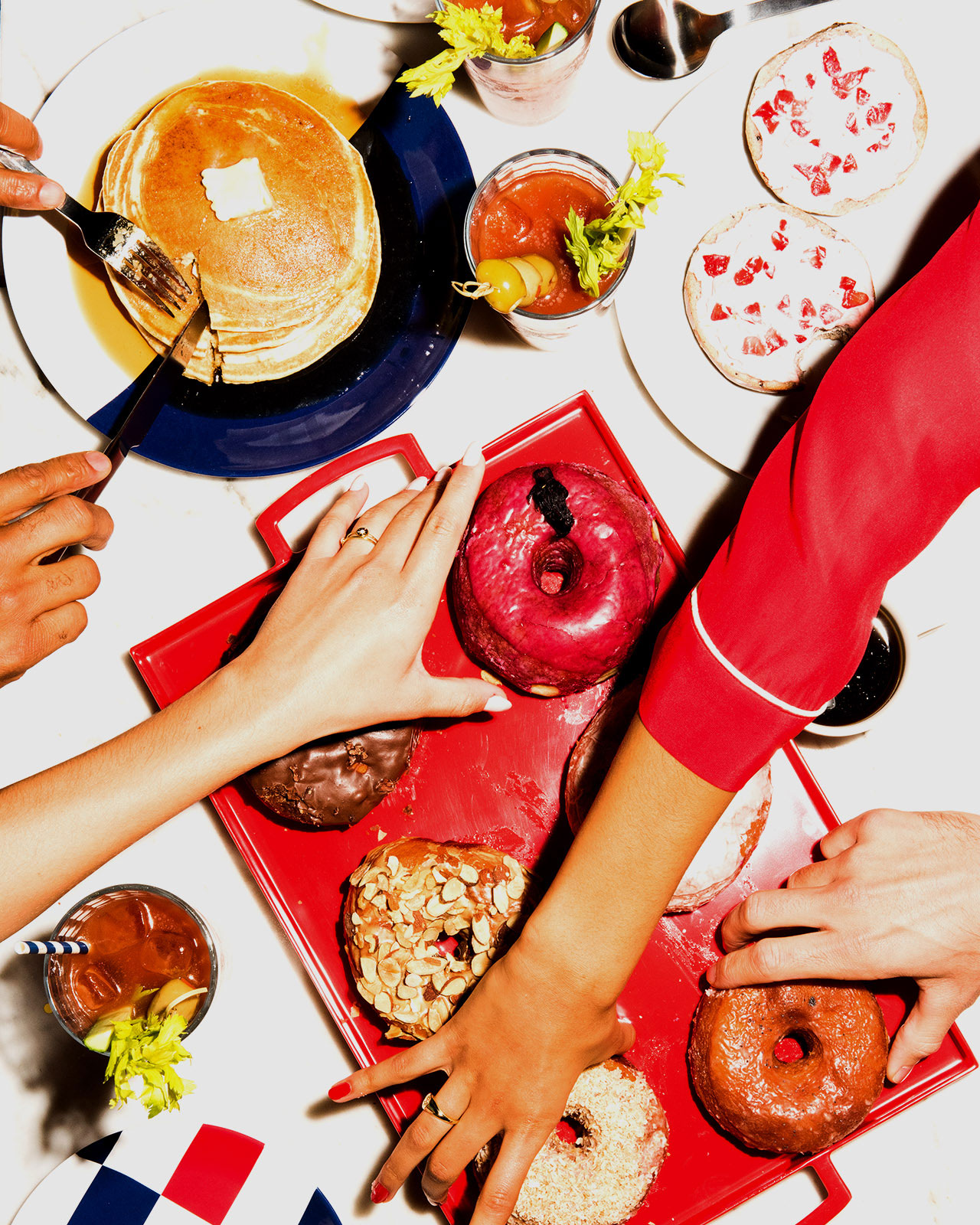 An overshot image of hands reaching for tasty bites like donuts, pancakes and bloody marys.