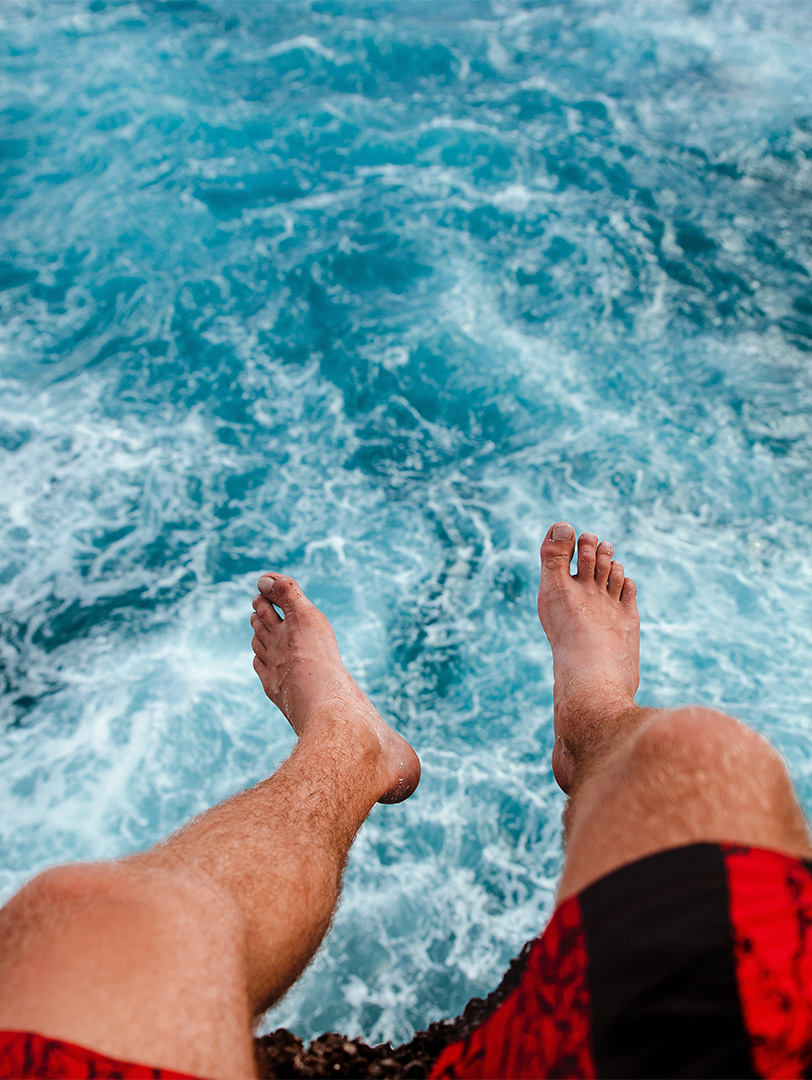 An overhead shot of a man's feet dangling over the ocean.